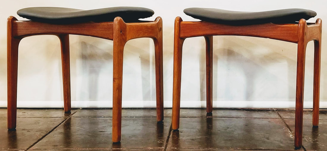 Eric Buch designed stools in teak wood with a black floating saddle seat. Designed about 1950.