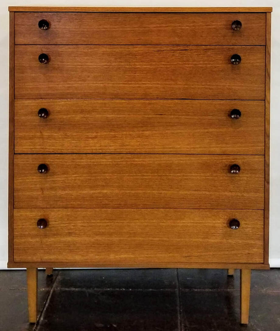 Mid-Century Modern five drawer chest constructed of teak wood with African afrormosia drawer pulls and birch peg legs.